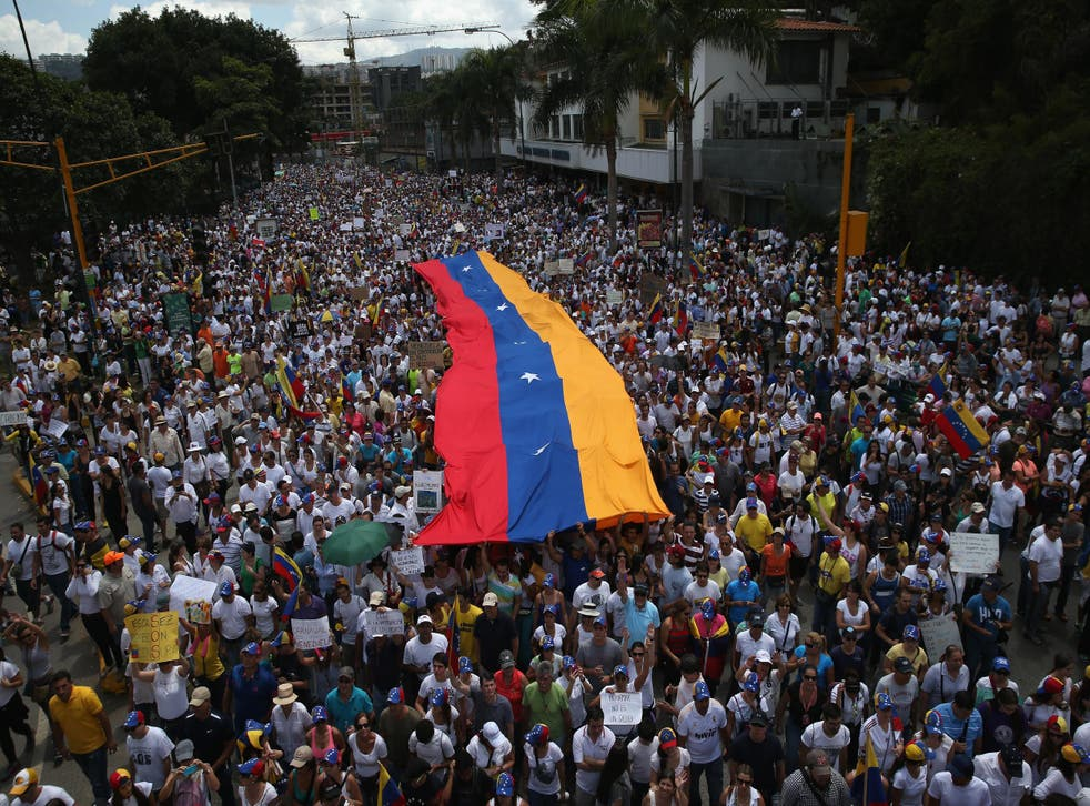 Carrying a giant Venezuelan flag, thousands of anti-government protesters march during a mass demonstration