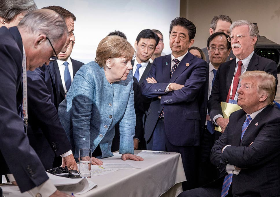 French President Emmanuel Macron, German Chancellor Angela Merkel and Japan's Prime Minister Shinzo Abe speaking to US Presidend Donald Trump during the second day of the G7 meeting in Charlevoix, Canada. Looking on is US National Security Advisor John R. Bolton.