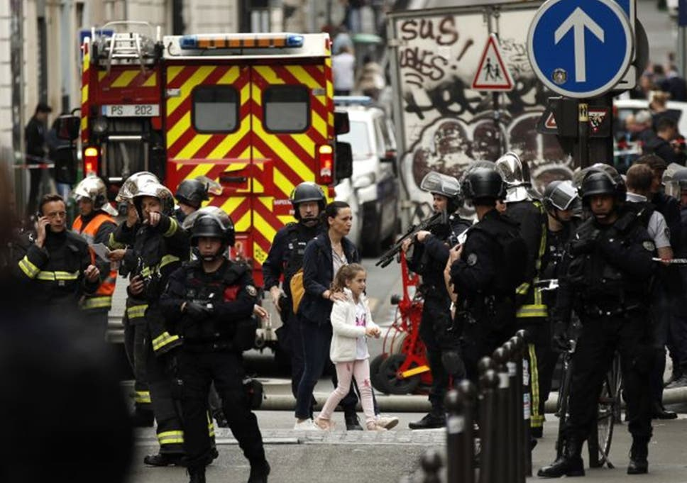 A woman and a young girl are evacuated by police forces during a hostage taking situation in Rue des Petites Ecuries, in Paris, France