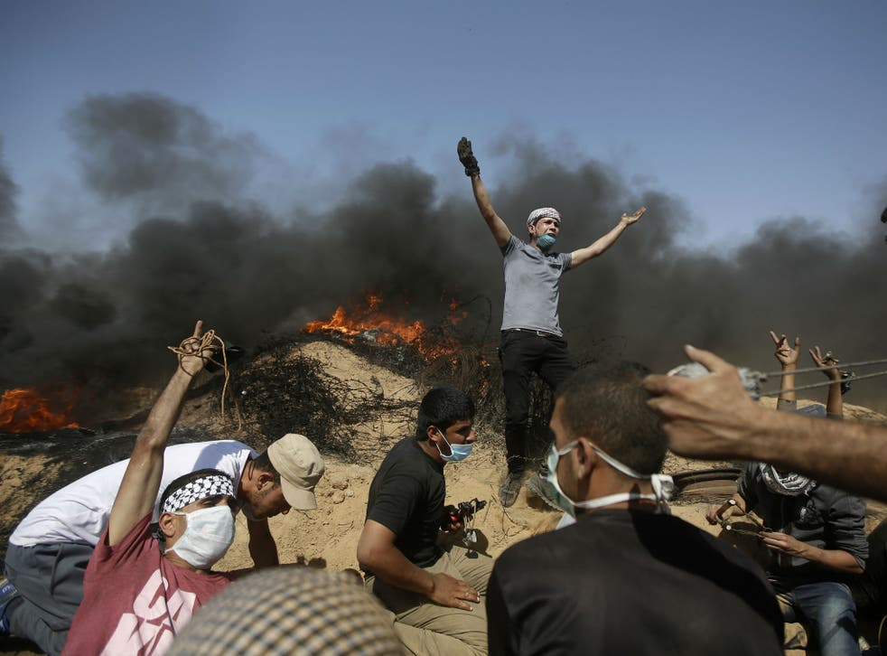 Palestinians take cover near the Gaza Strip's border with Israel during a protest in the Gaza Strip