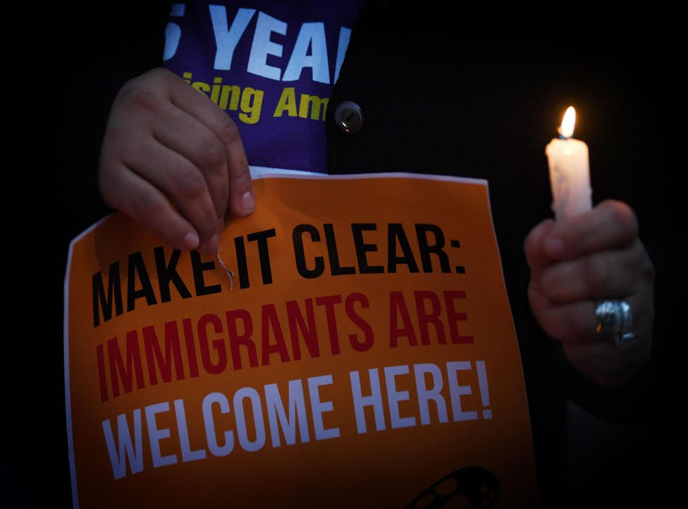 Migrant rights groups hold candles during a vigil to protest against US President Donald Trump's new crackdown on 'sanctuary cities', outside the City Hall in Los Angeles