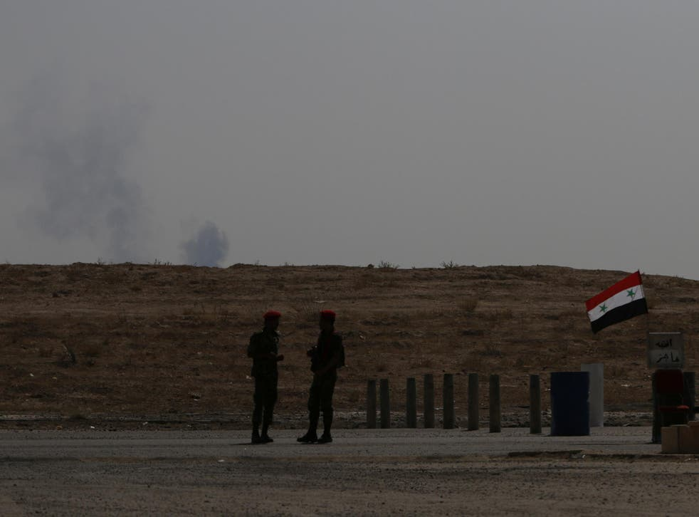 Smoke rises as Syrian army soldiers stand near a checkpoint in Deir Ezzor in this file photo from 21 September, 2017