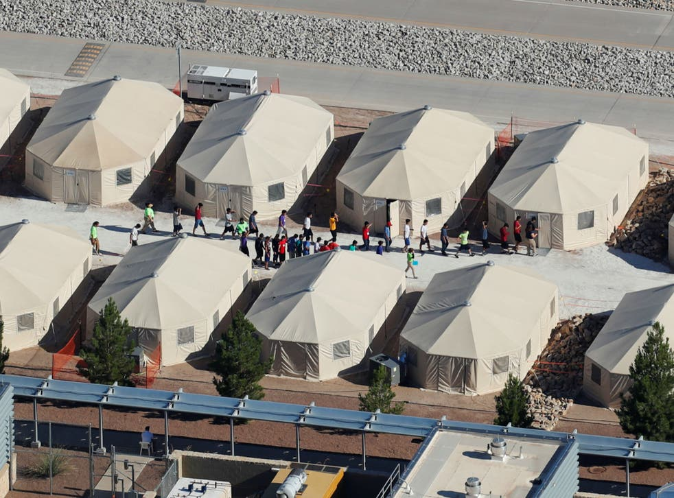 Immigrant children, many of whom have been separated from their parents under a new 'zero tolerance' policy by the Trump administration, are shown walking in single file between tents in their compound next to the Mexican border in Tornillo, Texas