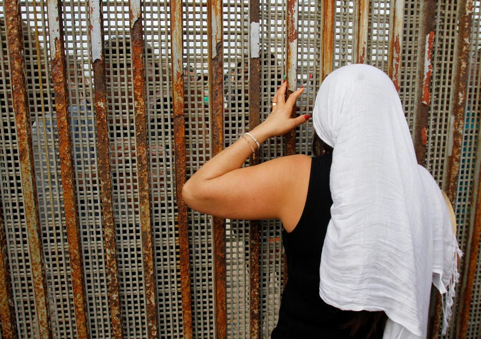 A Mexican woman talks with relatives through the fence that runs along the Mexico/US border in Tijuana, on Universal Children's Day 2016