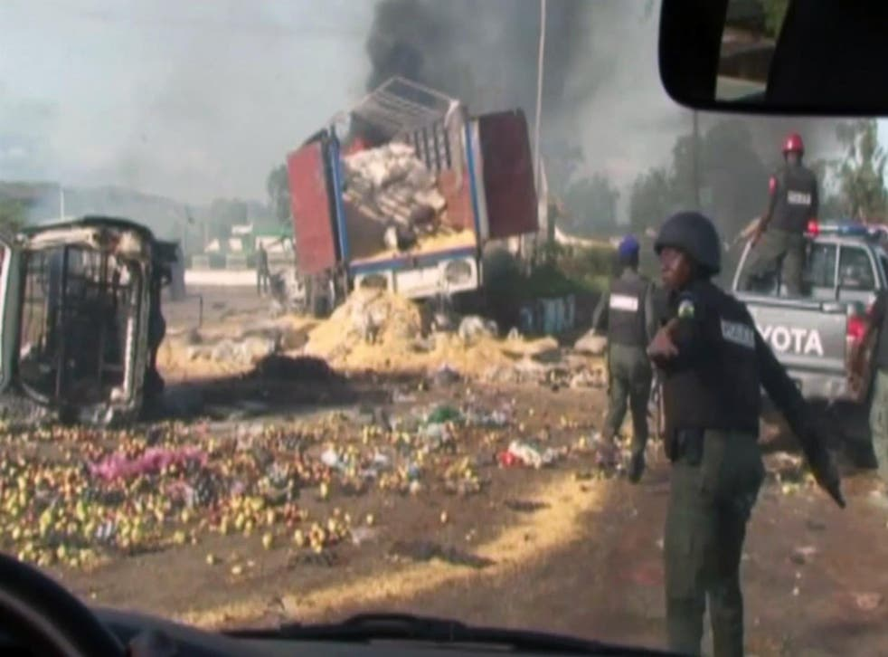 Destroyed vehicles and debris is strewn across the road as police attempt to restore calm in the town of Jos, Nigeria