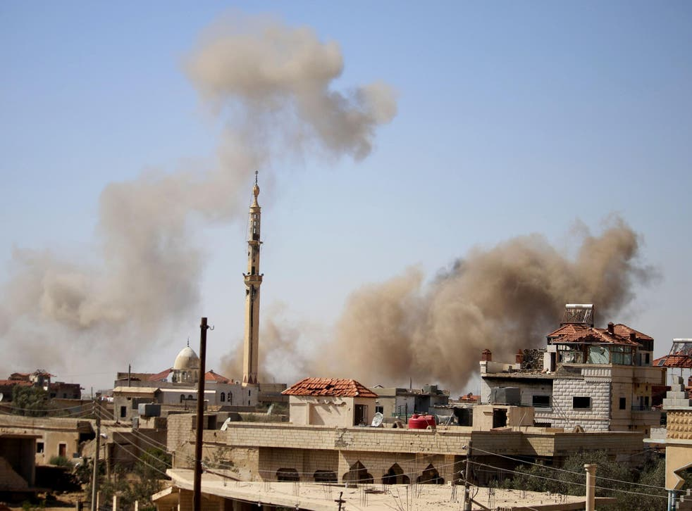 Smoke rises above buildings during an airstrike by Syrian regime forces on the town of Busra al-Harir, east of Daraa