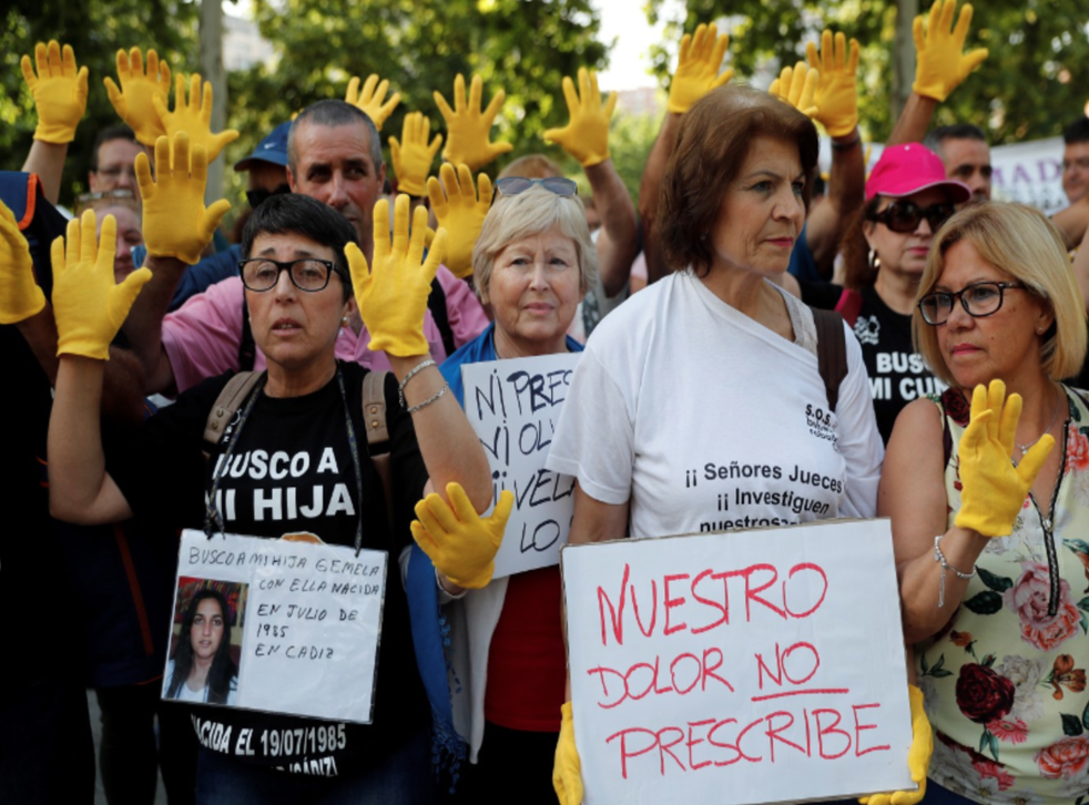 Protesters hold banners reading 'I'm looking for my twin daughter born with her in July 1985 in Cadiz' and 'our pain has no statute of limitations' at the Provincial Court in Madrid, Spain