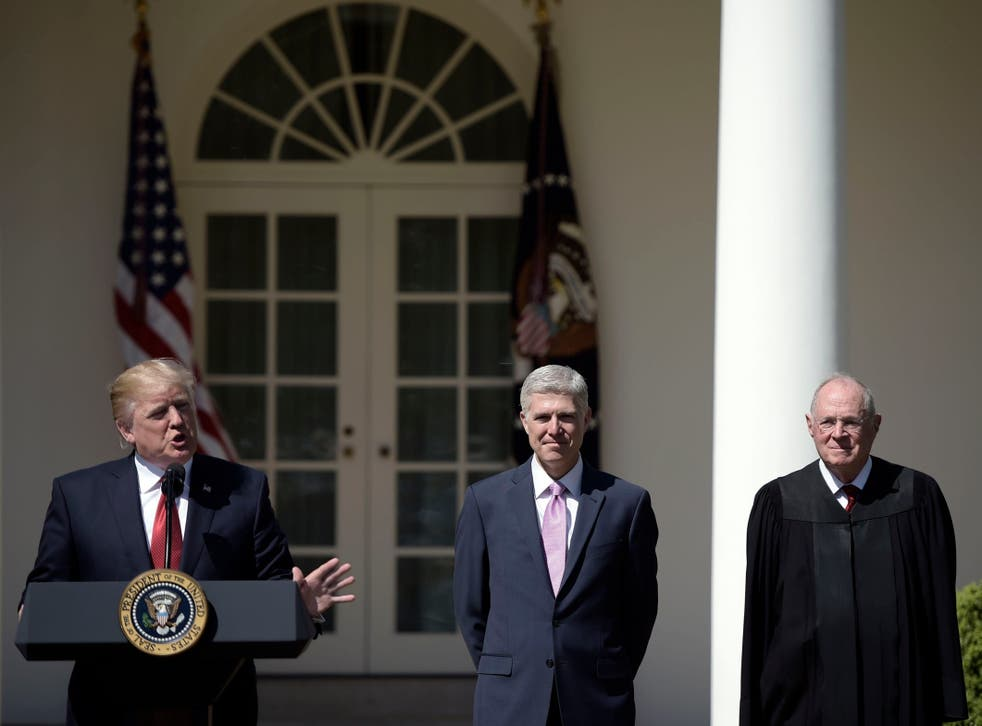 Donald Trump speaks before Justice Anthony Kennedy (R) administers the oath of office to Neil Gorsuch (C) as an associate justice of the US Supreme Court