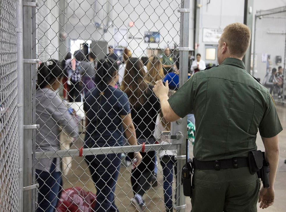 A US border patrol agent oversees migrants as they are processed at an immigrant detention centre
