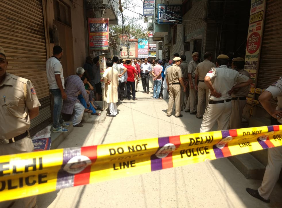 Police investigate at the house where 11 members of a family were found dead in New Delhi, India