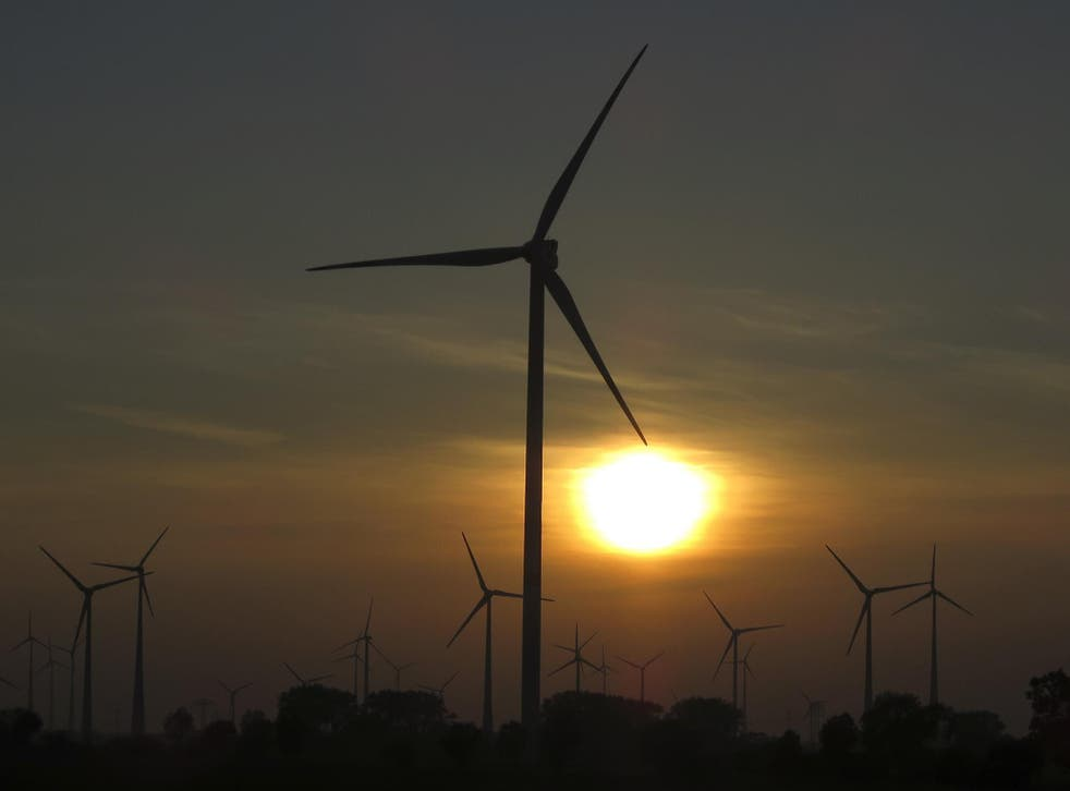 The sun sets behind power-generating wind turbines from a wind farm near the village of Ludwigsburg, northern Germany