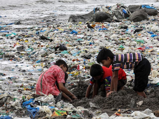 Indian children play amid leftovers and plastic waste at Mahim beach in Mumbai