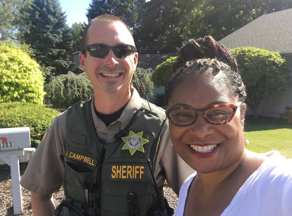 Oregon State Representative Janelle Bynum takes a picture with Officer Campbell of the Clackamas County Sheriff's office after a voter called police to report the candidate for campaigning door-to-door