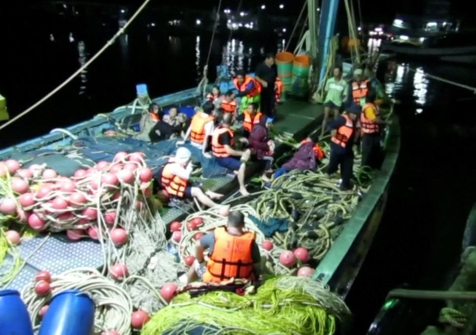 Rescued people in life jackets sit on a fishing boat after a boat they were travelling in capsized off Phuket