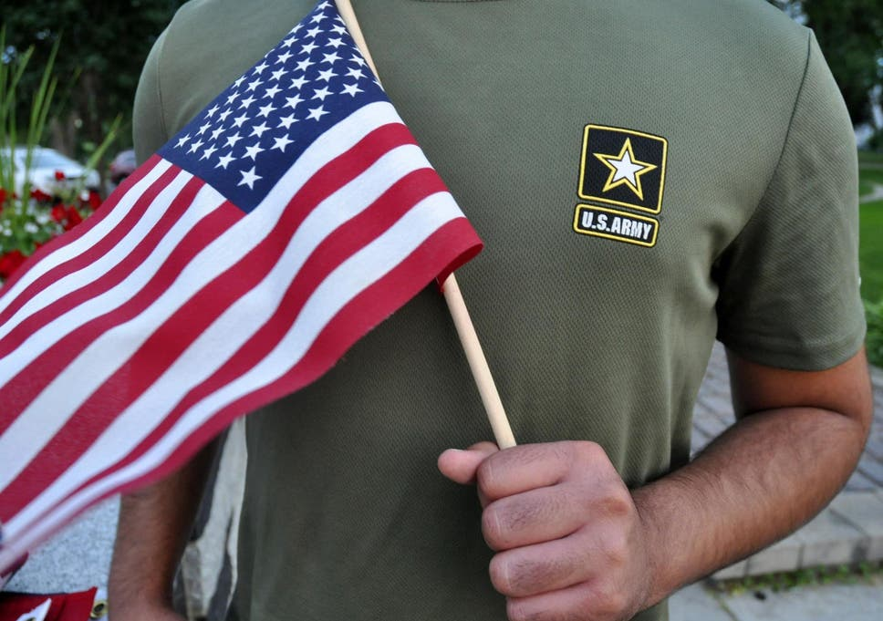 A Pakistani recruit, recently discharged by the US Army, holds an American flag