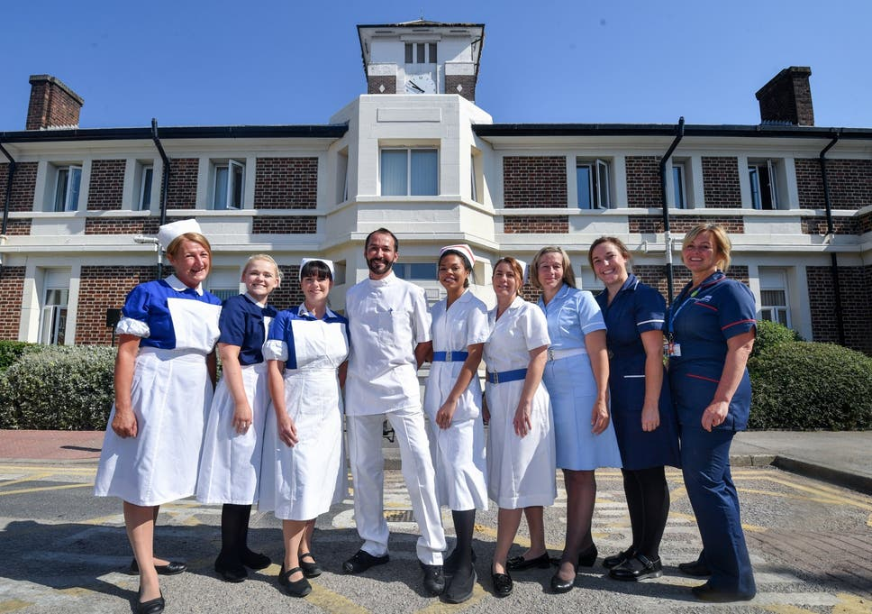 Nurses In Uniforms To Represent Each Decade Of The NHS Pose Outside Trafford Hospital Celebrate