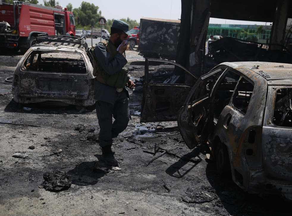 Afghan security officials inspect the scene of the attack that targeted the National Directorate of Security soldiers in Jalalabad
