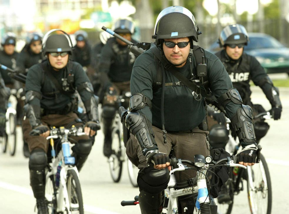 Riot police ride bicycles on Biscayne Boulevard in Florida.