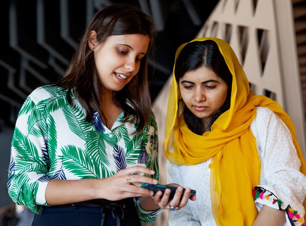 Brazilian student Beatriz Magalhães shows her project work to Malala Yousafzai in Rio de Janeiro on Friday