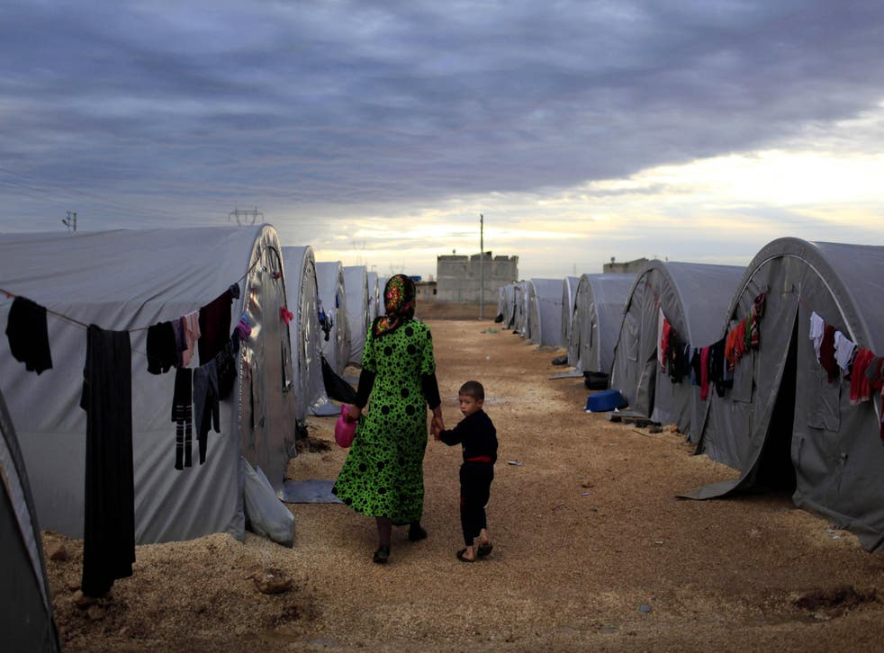 A Syrian woman and her child walk beside their tent in a camp in the southeastern town of Suruc on the Turkish-Syrian border in this file photo from 19 October, 2014