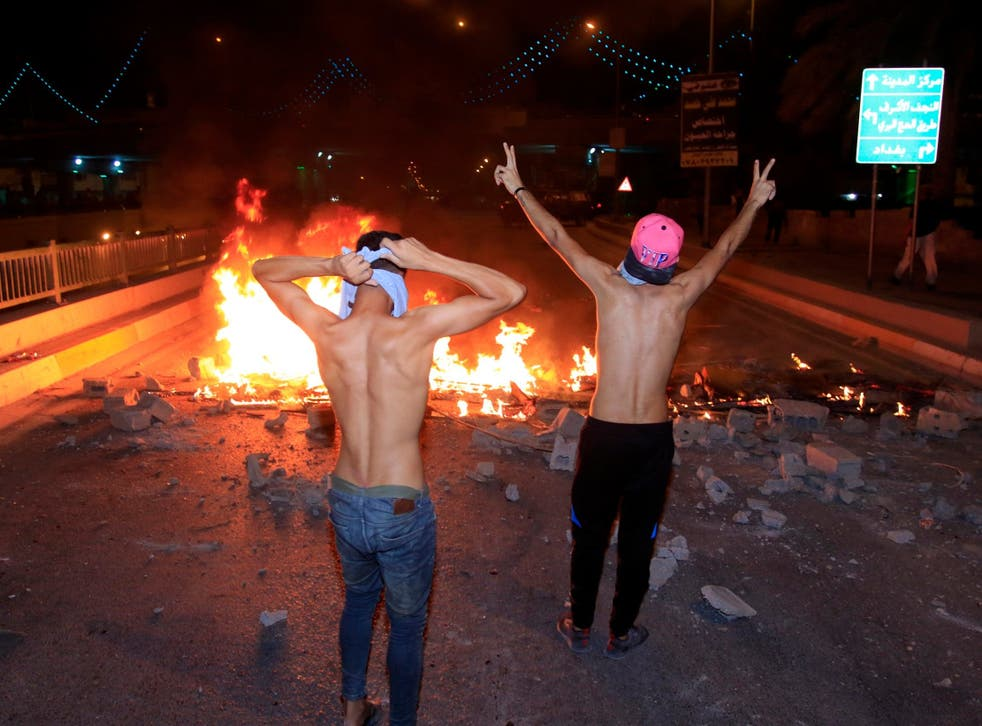 Iraqis burn tyres during a demonstration in Karbala city, southern Iraq