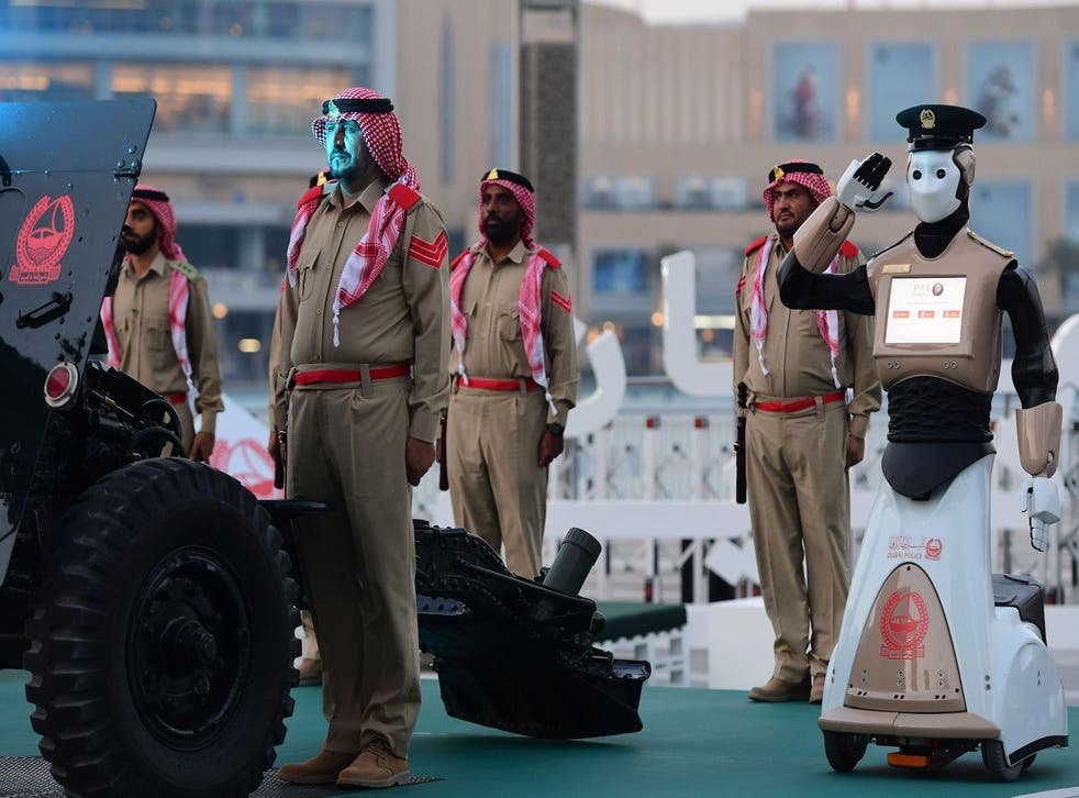 The world's first operational police robot stands at attention as they prepare a military cannon to fire to mark sunset and the end of the fasting day for Muslims observing Ramadan, in Downtown Dubai on May 31, 2017