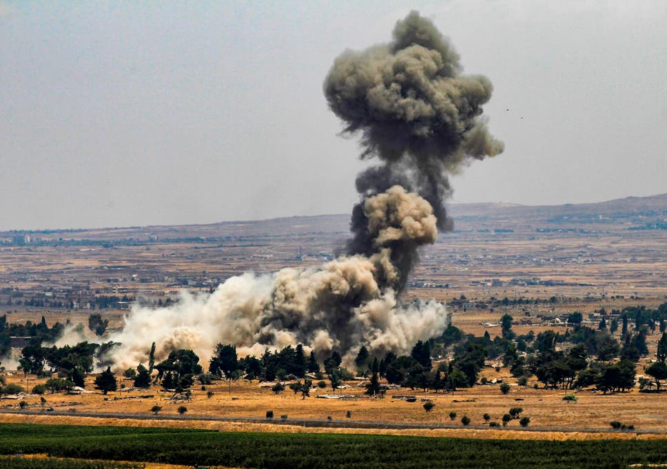 Quneitra in Syria viewed from the Israeli-annexed Golan Heights – smoke rises as rebels destroy their arms stocks prior to their departure