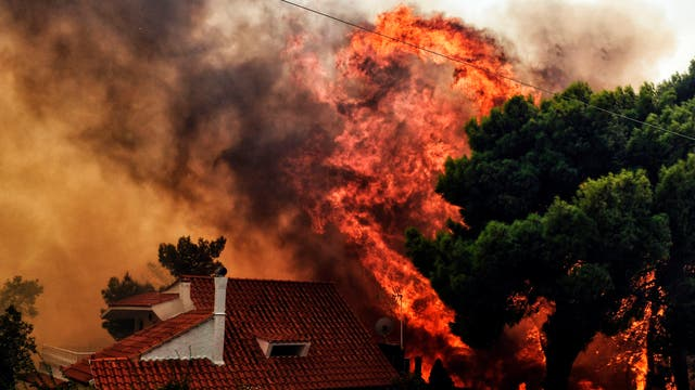 A house threatened by a huge blaze during a wildfire in Kineta