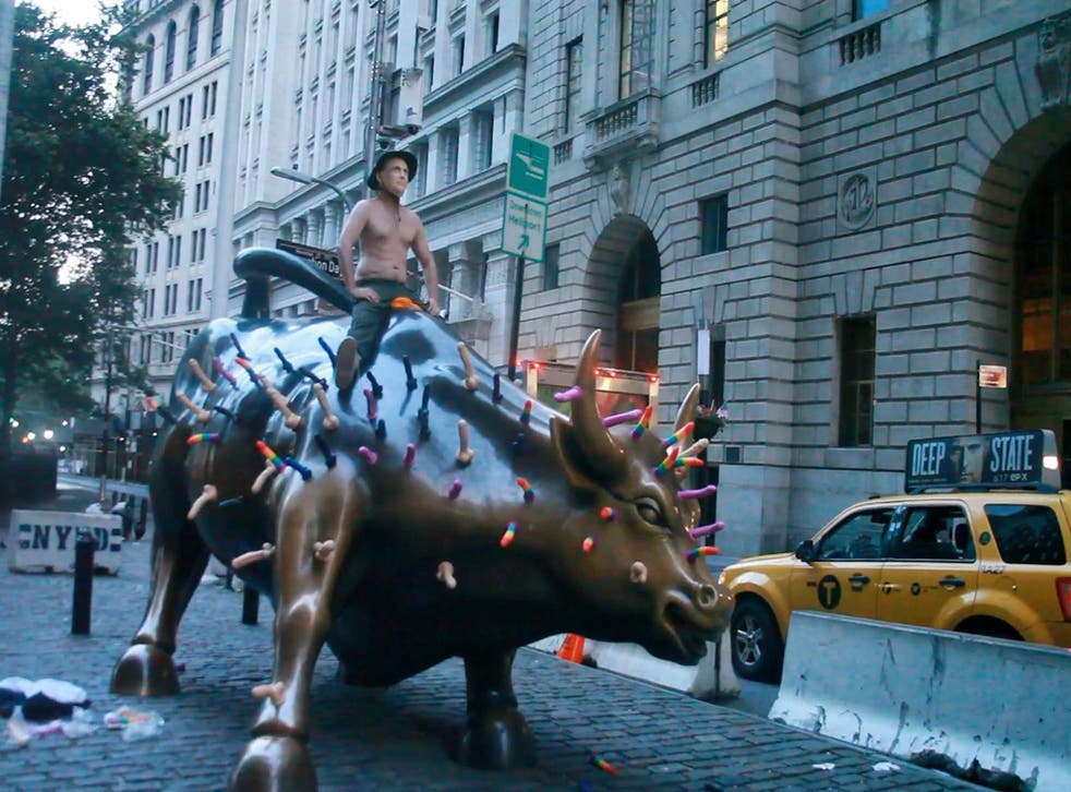 Activist Jeff Jetton, bare chested and wearing a mask to portray Russia's President Vladimir Putin, sits on the Wall Street bull sculpture covered with sex toys in a still image from video taken in New York City, U.S. July 16, 2018.