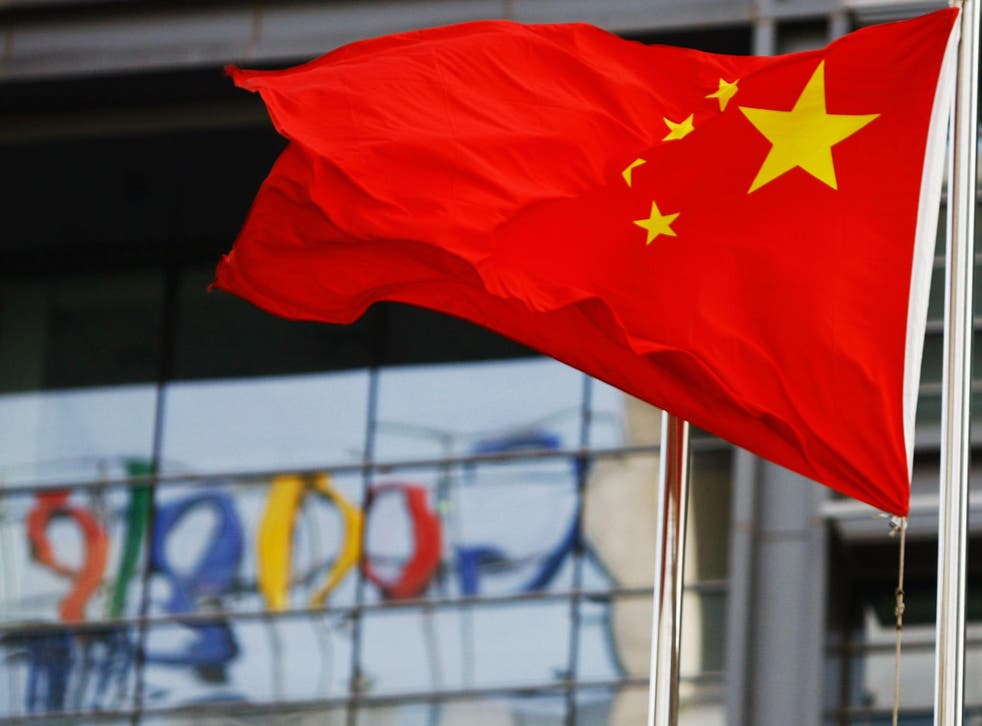 The Google logo is reflected in windows of the company's China head office as the Chinese national flag flies in the wind in Beijing on March 23, 2010