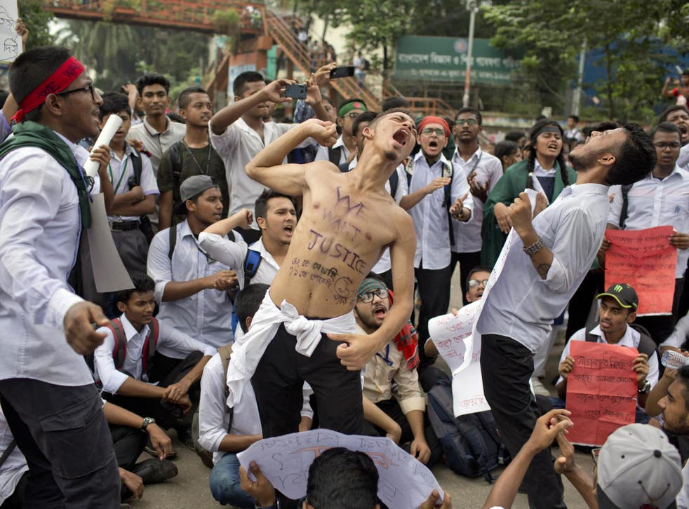Students shout slogans and block a road during a protest following two people's deaths