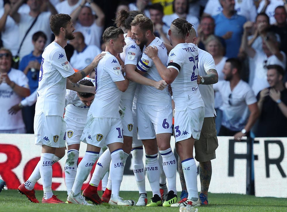 Liam Cooper celebrates with his teammates after scoring Leeds' third goal