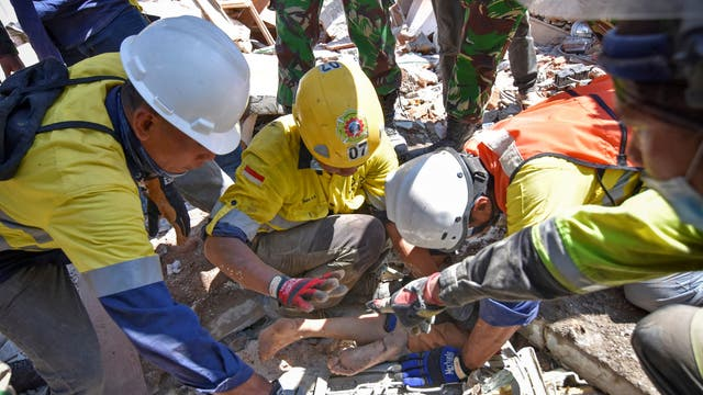 Rescue workers extract a woman, who survived after being trapped in rubble since the earthquake in Lombok, Indonesia