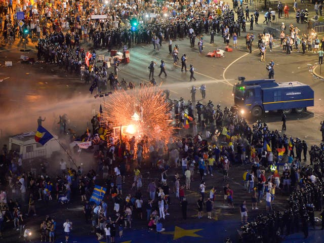 A teargas canister explodes as riot police charge using water canons to clear the square during protests outside the government headquarters in Bucharest