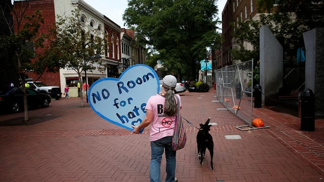 "Mary Grace, from Durham, North Carolina, walks through the downtown mall area August 11, 2018 in Charlottesville, Virginia. Charlottesville has been declared in a state of emergency by Virginia Gov. Ralph Northam as the city braces for the one year anniversary of the deadly clash between white supremacist forces and counter protesters over the potential removal of Confederate statues of Robert E. Lee and Jackson. A ""Unite the Right"" rally featuring some of the same groups is planned for tomorrow in Washington, DC."