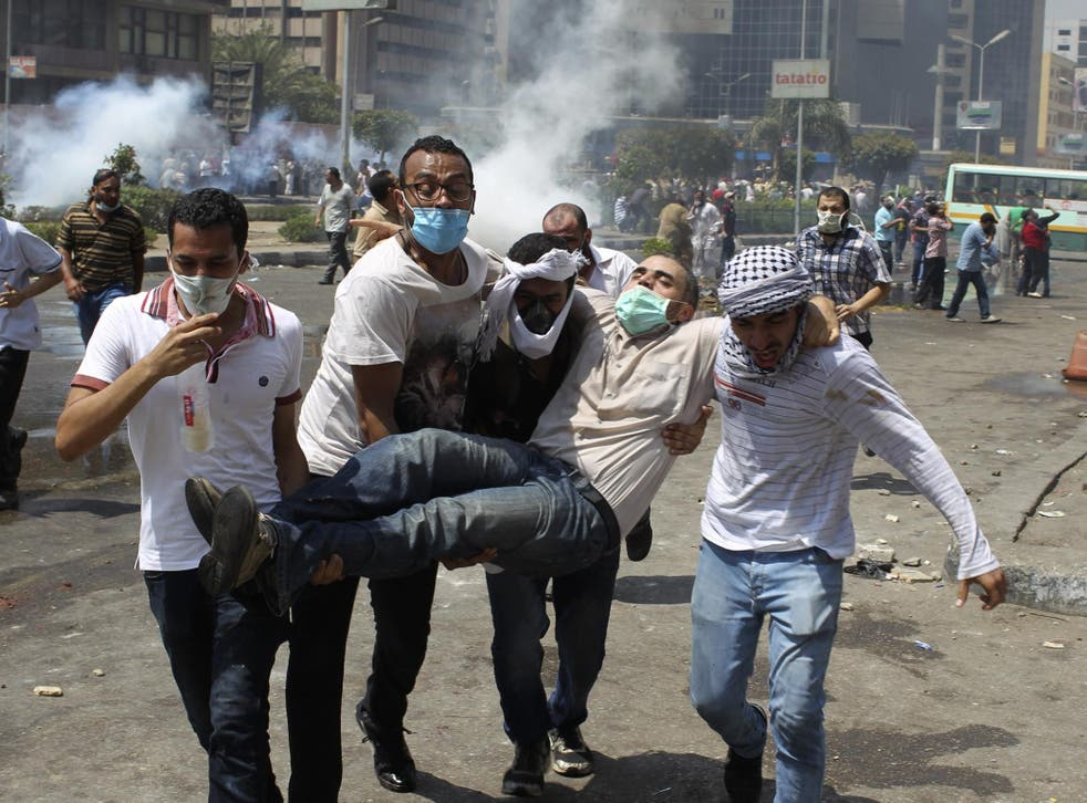 Supporters of deposed Egyptian president Morsi carry an injured protester from Cairo's Rabaa square