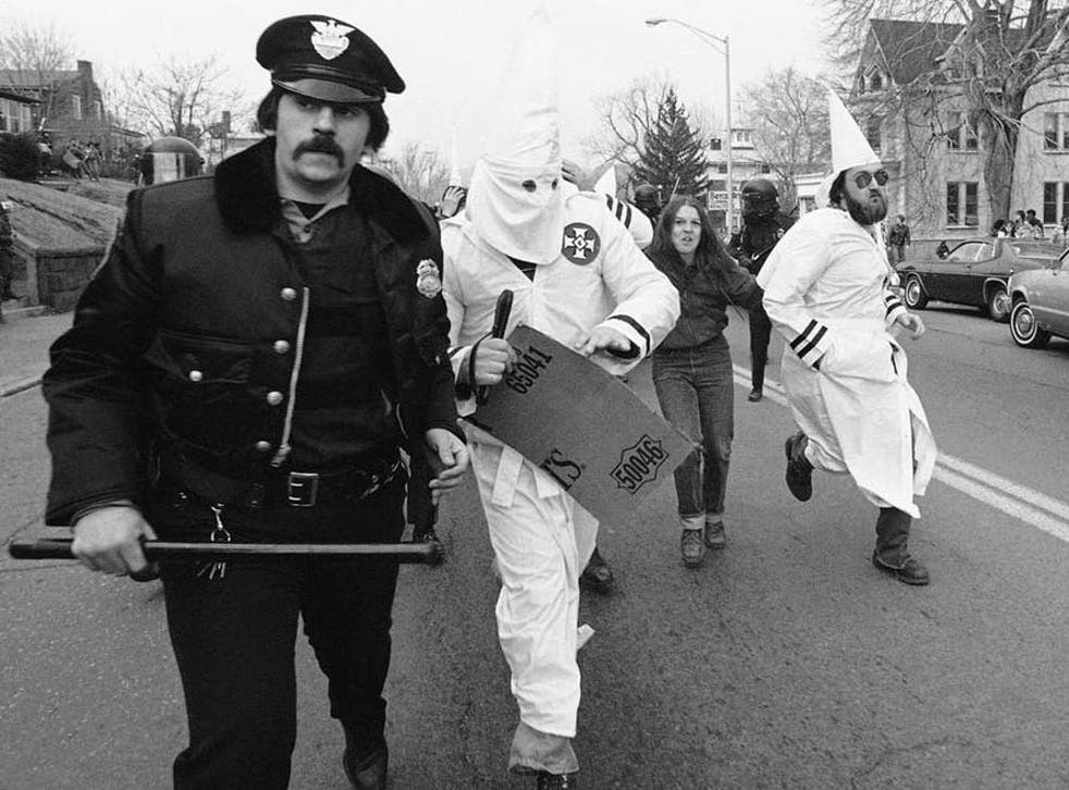Ku Klux Klan members are escorted away from protesters by police in Meriden, Connecticut, 1981