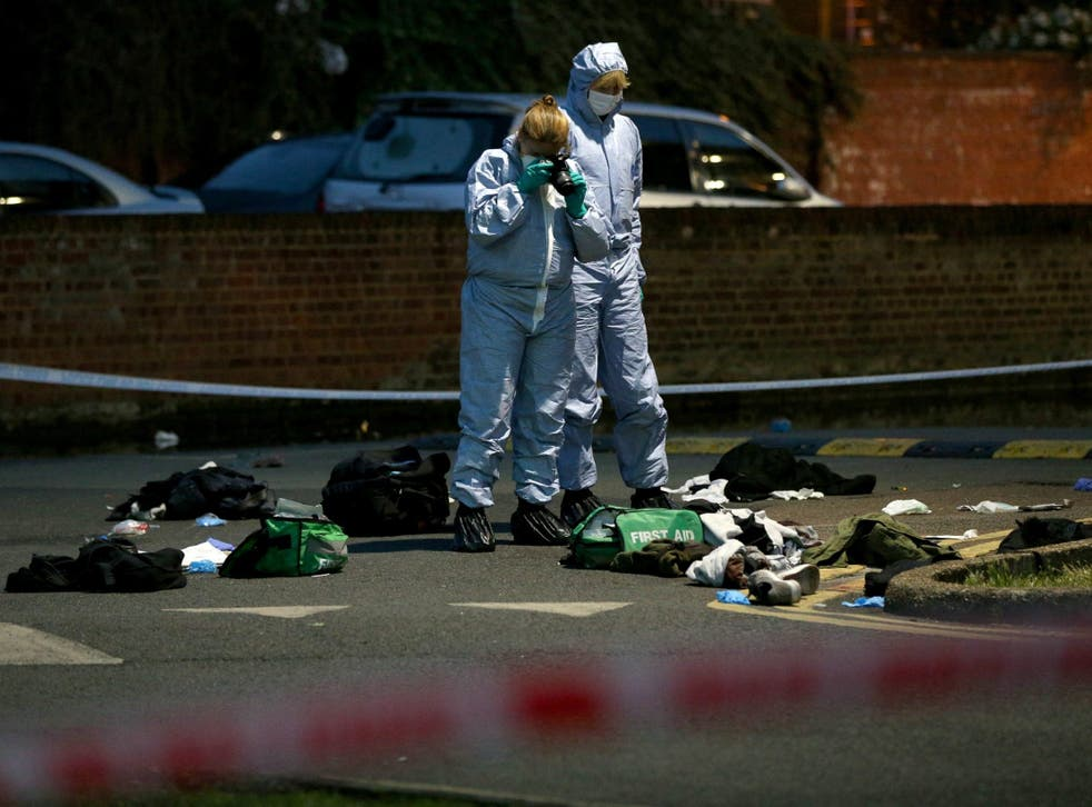 Forensics officers inspect the area outside Landor House, Camberwell, London, after four people were taken to hospital with stab wounds
