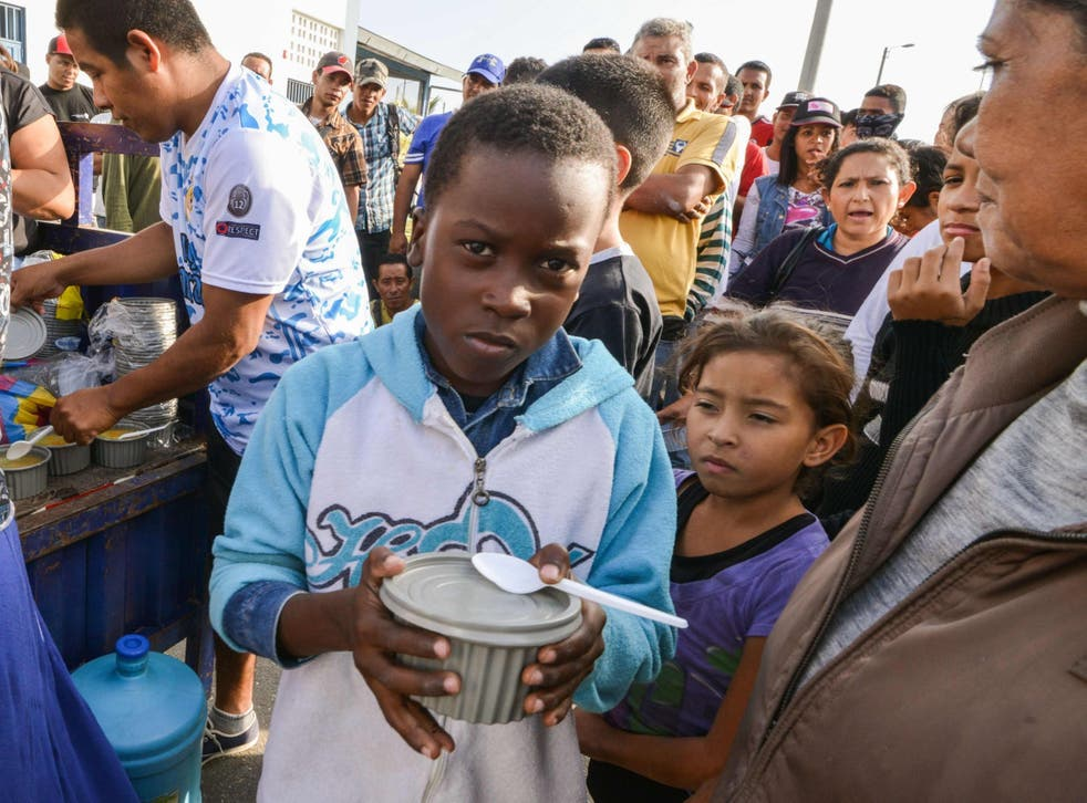 Venezuelan nationals receive food from religious volunteers while they wait for an authorisation that will allow them to enter Peru.