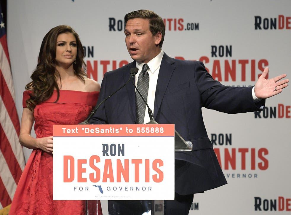 El candidato republicano a gobernador de Florida, Ron DeSantis, a la derecha, habla a sus partidarios con su esposa, Casey, en un partido electoral después de ganar las primarias republicanas.