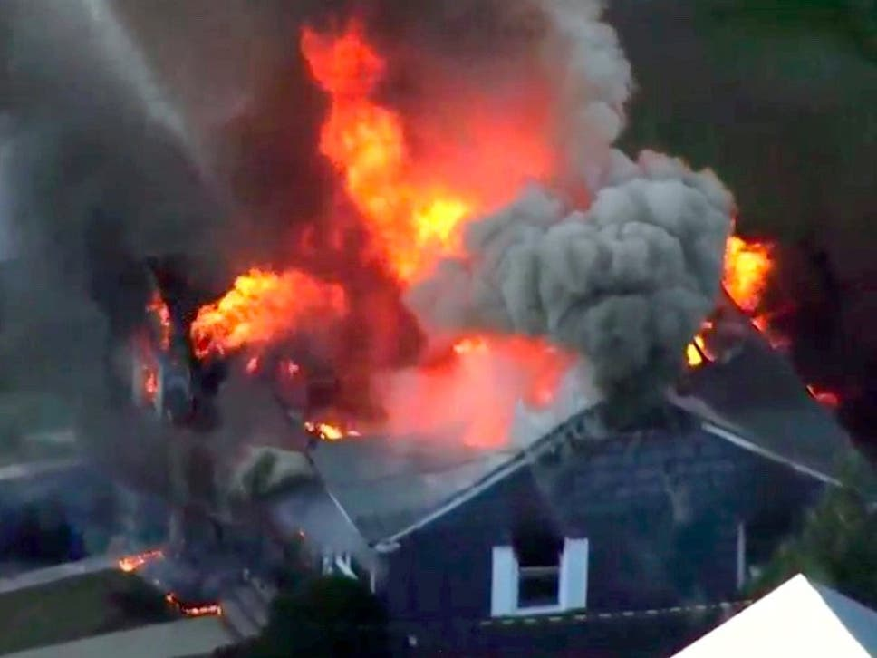 Image from video provided by WCVB in Boston, showing flames consume a home in Lawrence