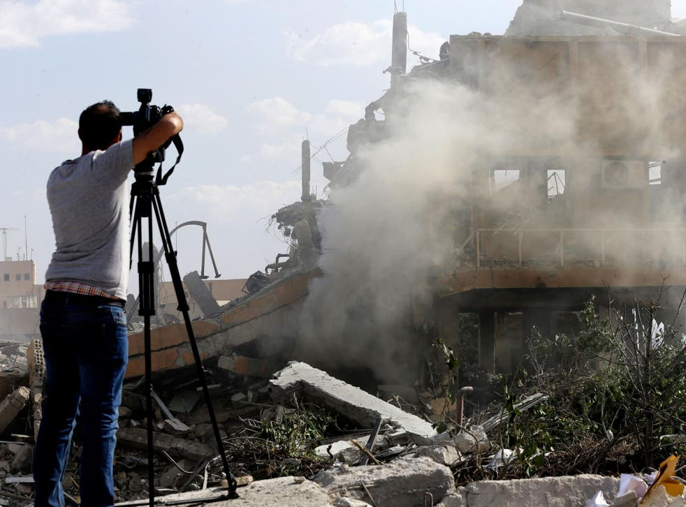 A journalist films the wreckage of the Scientific Studies and Research Centre in Barzeh, southern Syria, in 2018