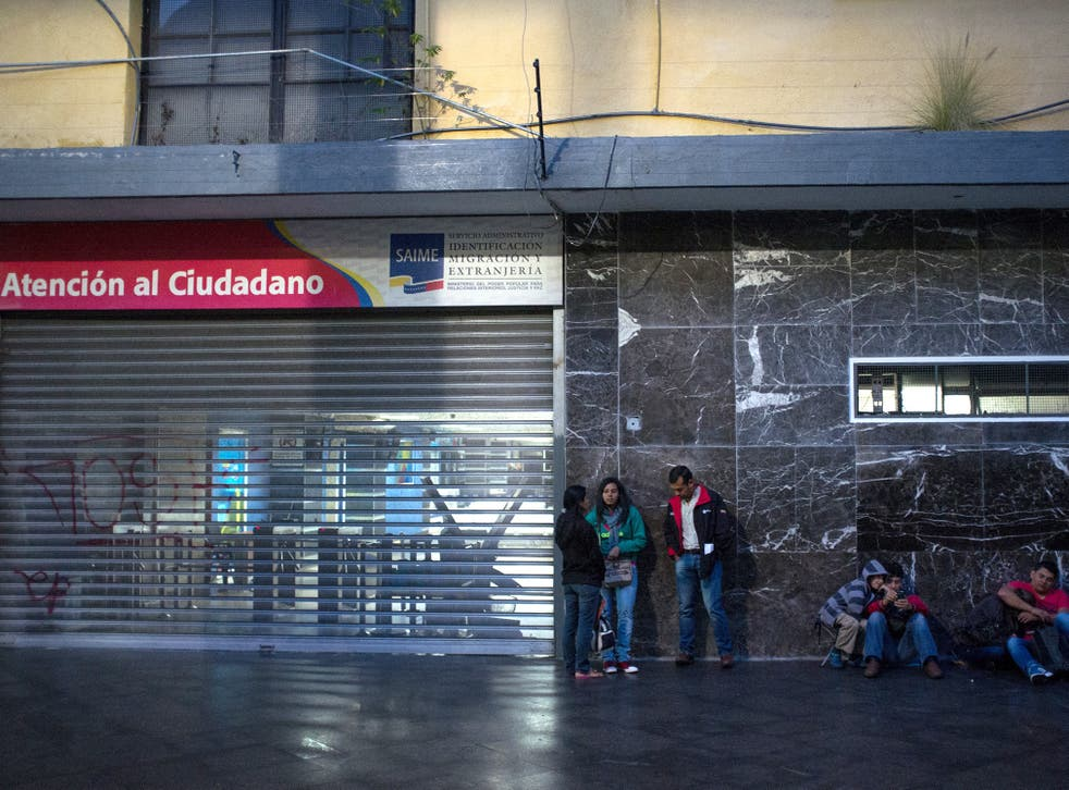 People wait in line outside Saime offices in Caracas