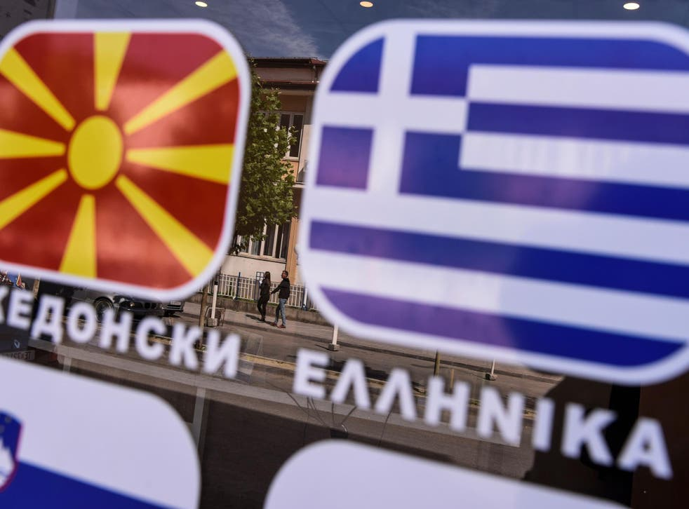 People are reflected on a window bearing the flags of Macedonia and Greece in the town of Tetovo, near Skopje