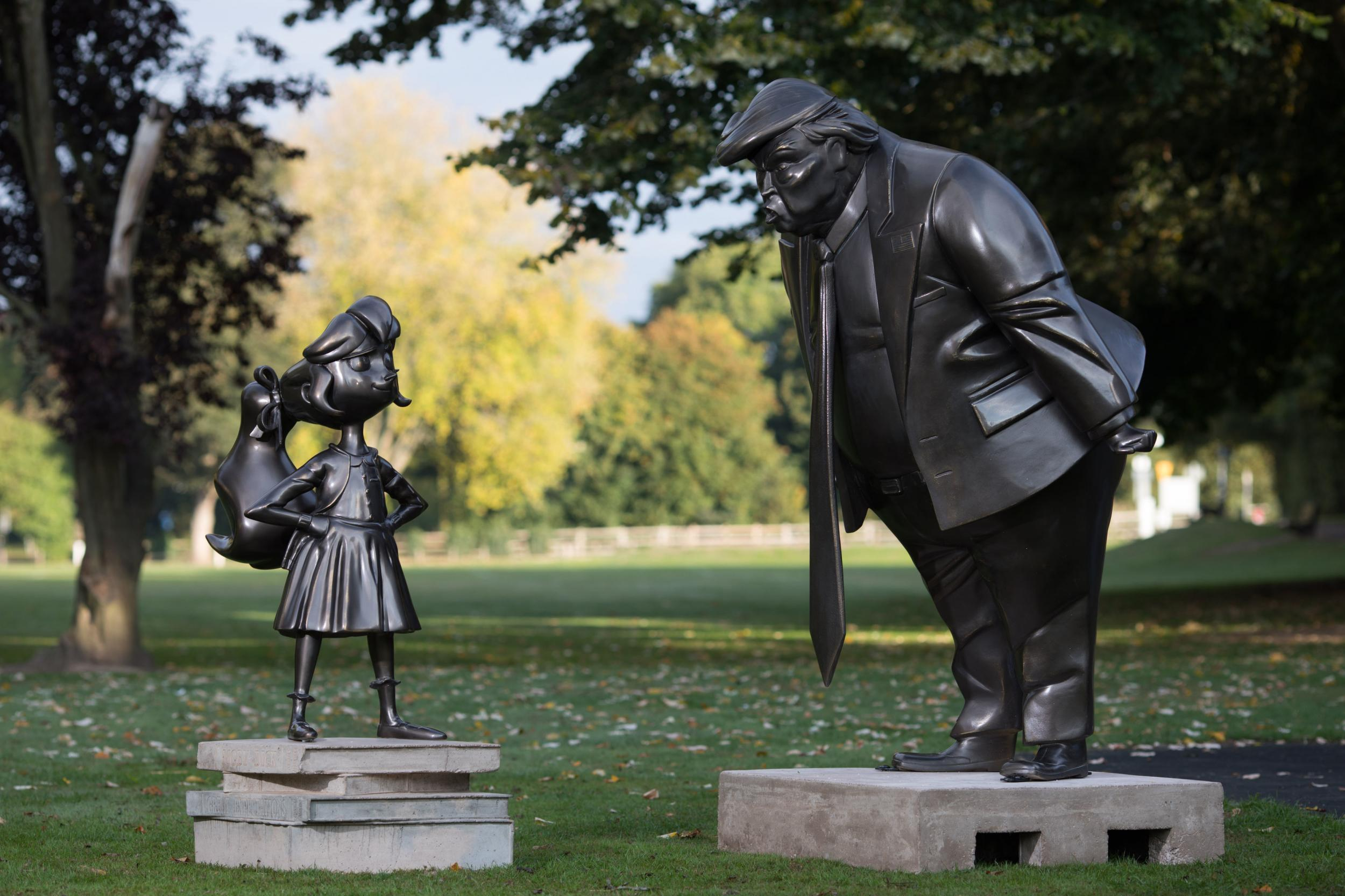 Matilda statue standing defiantly in front of Trump