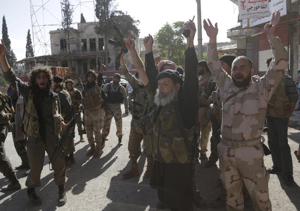 Members of the former al-Qaeda affiliate in Syria, now called Hayat Tahrir al-Sham, gesture as they cheer in the northwestern city of Ariha, after a coalition of insurgent groups seized the area in Idlib province on 29 May 2015