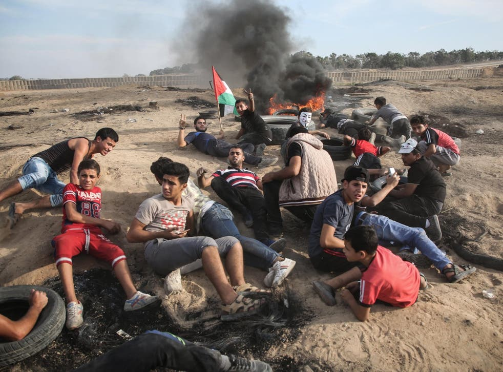 Palestinians take cover at protest on the Gaza-Israel border on 5 October