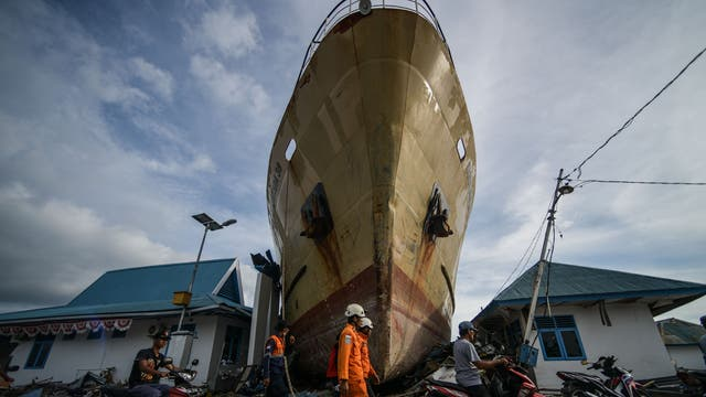 Residents and rescuers walk in front of a washed out passenger ferry in Wani following the September 28 earthquake and tsunami. Aid poured into disaster-ravaged Palu after days of delays as efforts ramped up to reach 200,000 people in desperate need