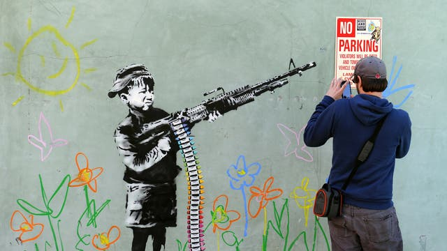 A Banksy piece in California depicting a child wielding a machine gun, in black and white surrounded by colored flowers