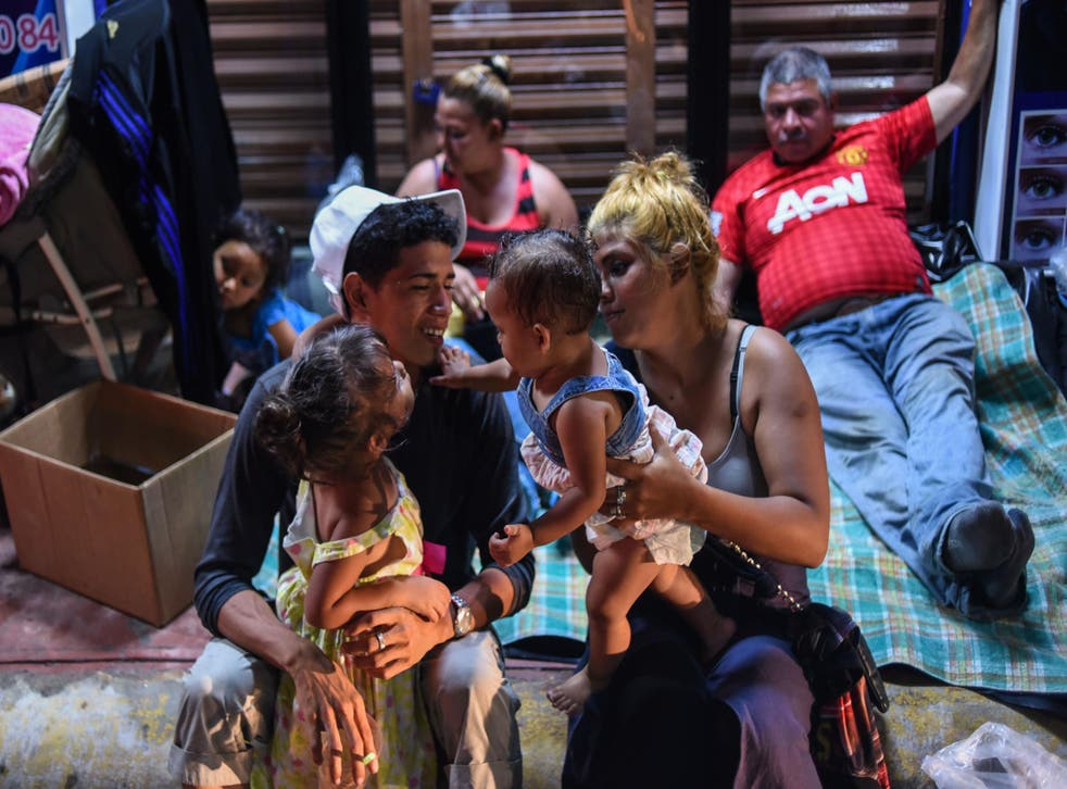 A Honduran migrant family taking part in a caravan heading to the US, rest on their arrival to Huixtla, Chiapas state, Mexico, on 22 October 2018.